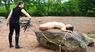 The Mistress whips a naked submissive lying on a large stone. This is a punishment for poorly washed dishes